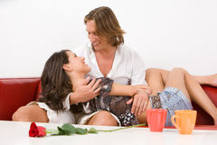 Young couple laughing on the sofa Stock Photo
