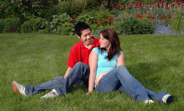 Young couple on a lawn. Young couple relax in a garden Royalty Free Stock Image