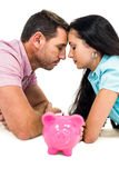 Young couple laying on the floor face to face with piggybank Stock Photography