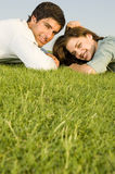 A young couple laying on grass Royalty Free Stock Photography