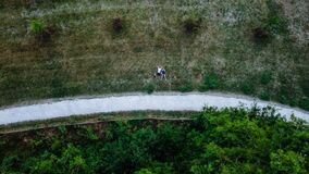 Young couple laying on the grass, drone photo, aerial perspective, bird`s eye view