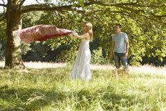 A young couple laying a picnic blanket on the grass Royalty Free Stock Images