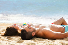 Young couple laying on sandy beach at sea shore Royalty Free Stock Photo