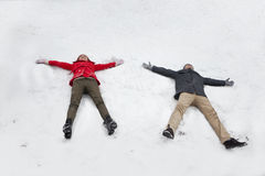 Young couple laying in snow making snow angels Royalty Free Stock Photography