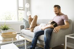 Young couple laying on the sofa relaxing at home. A Young couple laying on the sofa relaxing at home royalty free stock photos