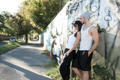 Young Couple leaning against a wall in a urban environment Royalty Free Stock Image