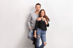Young couple leaning against a white wall. And looking at the camera Royalty Free Stock Photo