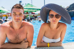 Young Couple Leaning on Edge of Swimming Pool Stock Photo