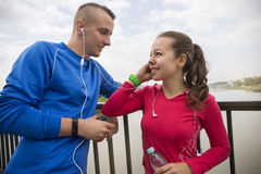 Young couple leaning on rail listening music on the earphones Royalty Free Stock Image
