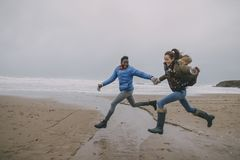Young Couple Leap Along A Winter Beach Stock Images
