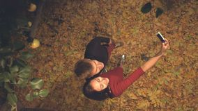 Young couple in leaves is photographed itself. Slow motion. Top view. The guy and the girl are standing in the evening among the yellow leaves. They take stock video footage