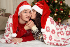 Young couple lie in christmas decoration. Home interior with gifts and fir tree. New year holiday concept. Love and tenderness. Stock Photos