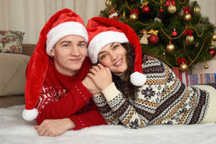Young couple lie in christmas decoration. Home interior with gifts and fir tree. New year holiday concept. Love and tenderness. Stock Photography