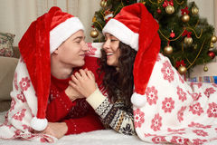 Young couple lie in christmas decoration. Home interior with gifts and fir tree. New year holiday concept. Love and tenderness. Stock Image