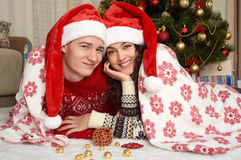 Young couple lie in christmas decoration. Home interior with gifts and fir tree. New year holiday concept. Love and tenderness. Royalty Free Stock Photo