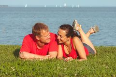 Young couple lies on the shore in lake Balaton in Hungary stock photo