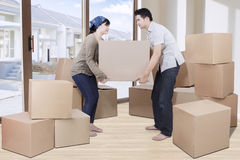 Young couple lift cardboard in new house Stock Photography