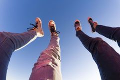 Young couple lifts their legs to the sky. Young couple lifts their legs towards clear blue sky Royalty Free Stock Images