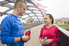 Young couple listening music on the earphones. Happy young couple leaning on rail listening to music on the earphones smiling and laughing after jogging Stock Images