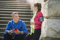 Young couple listening music on earphones. Happy young couple listening to music on the earphones smiling and laughing after jogging Royalty Free Stock Photography