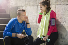 Young couple listening music on earphones on a sunny day. Happy young couple listening to music on the earphones smiling and laughing after jogging on a sunny Stock Photos