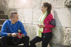 A young couple listening music on earphones on a sunny day. royalty free stock photography