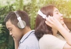 Young couple  listening music form headphone. Young couple standing in the park and listening music form headphone Stock Images