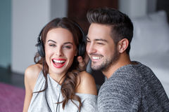 Young couple listening music by headphones indoor Stock Images