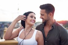 Young couple listening music by headphones looking to each other at outdoors stock image