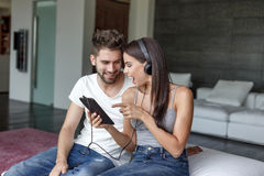 Young couple listening music indoor by headphones. And laughing Royalty Free Stock Photos