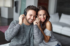 Young couple listening music indoors Royalty Free Stock Images