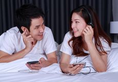 Couple listening music from mobile with headphone on bed. Young couple listening music from mobile with headphone on bed Royalty Free Stock Image