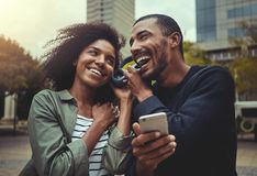 Young couple listening music on one headphone stock images