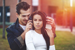 Young couple listening music outdoor in sunset. Outdoor Stock Photo