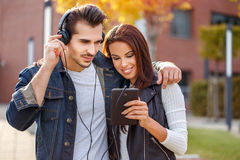 Young couple listening music outdoor on tablet. Young caucasian couple listening music outdoor on tablet Royalty Free Stock Photo
