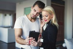 Young couple listening music by tablet at home. Young caucasian couple listening music by tablet at home Stock Images