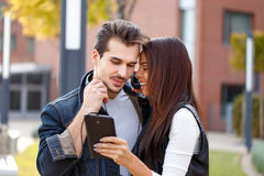 Young couple listening music on tablet. Outdoor Royalty Free Stock Image