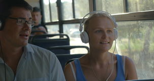 Young couple listening to music on headphones during the bus ride, they dance to the music, man singing stock footage