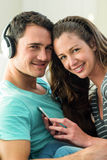 Young couple listening to music on mobile phone. Portrait of young couple listening music on mobile phone in living room Royalty Free Stock Images