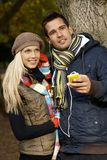 Young couple listening to music outdoors smiling Stock Photo