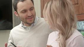 Young couple listening to music via smartphone, talking in the kitchen stock footage
