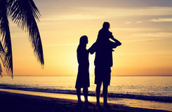 Young couple with little child at sunset tropical Stock Photos