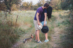 Young couple with little dog yorkshire terrier dressed  t-shirt and hat embracing and have fun on the road Royalty Free Stock Photography