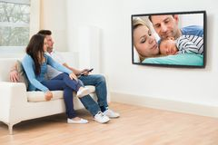 Young couple in livingroom watching television Stock Image