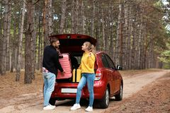 Young couple loading suitcases into car trunk royalty free stock images