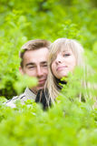 Young couple look out of green bushes Royalty Free Stock Photography