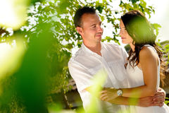 Young couple looking accomplices among trees. Young couple dressed in white looking accomplices among trees in the field Stock Photo