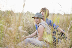 Young couple looking away while relaxing in field Stock Photo
