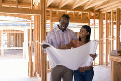 Young couple looking at blueprints in partially built house, smiling Stock Photography