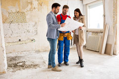 Young couple looking blueprints of their home with handyman Royalty Free Stock Photos